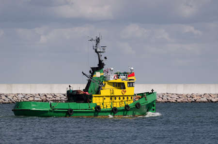 TUGBOAT - Auxiliary vessel is sailing on the background of breakwater