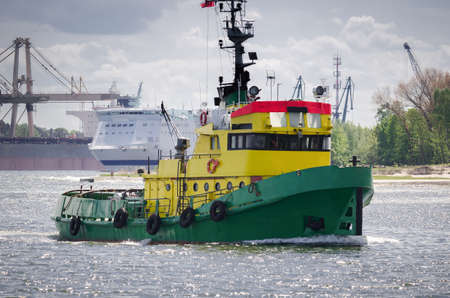TUGBOAT - Auxiliary vessel sails in the seaport background Standard-Bild