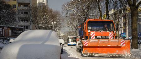 KOLOBRZEG, WEST POMERANIAN - POLAND - 2021: A snow plow is working on streets of the city 新聞圖片
