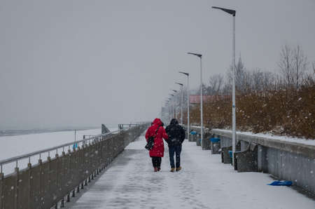 SEA COAST IN WINTER - Snowstorm on the promenade, a snowy beach and two peple on walk