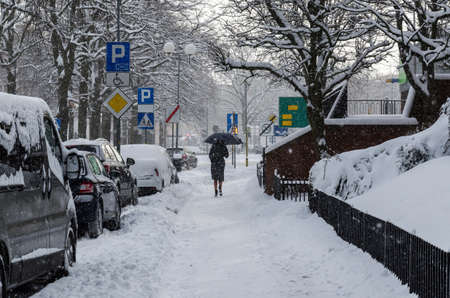 WINTER ATTACK - A woman with an umbrella is walking along the snowy pavement