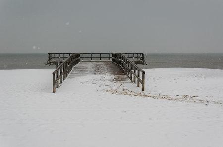 SEA COAST IN WINTER - Snowstorm over the beach and wooden pier 版權商用圖片