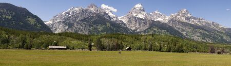 A panoramic view of a horse ranch with the Grand Tetons i n the background photo