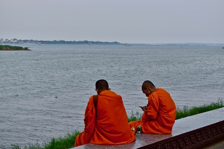 Two monks and the Mekong river in Phnom Penh, Cambodia.