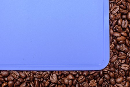 edges: Blue background around the edges of roasted coffee beans, space for text.