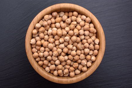 Peeled chickpeas lies in a wooden cup on a stony black board, black background, space for text.