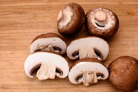 champignons: Gray mushrooms champignons lie on a wooden kitchen board. Stock Photo