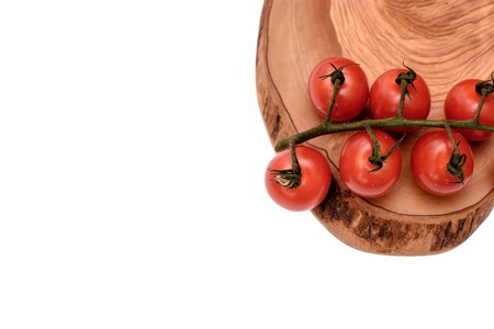 gusty: Cherry tomatoes lie on a wooden board of drying oil, isolated on white background. Stock Photo