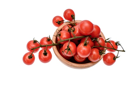 gusty: Red cherry tomatoes lie in a wooden cup, isolated on a white background.