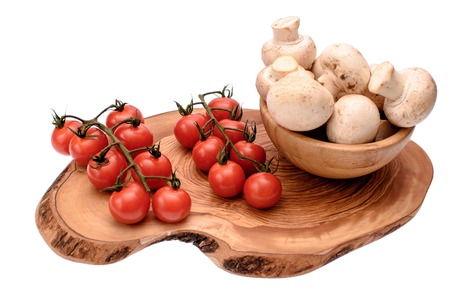 gusty: White mushrooms champignons and cherry tomatoes lie on a wooden board of drying oil, isolated on white background.