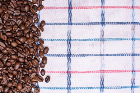 space for type: Texture of a colored towel, a towel of a cellular type, on which lies a certain amount of brown coffee beans. Top view with a bunch of coffee beans with space for text.