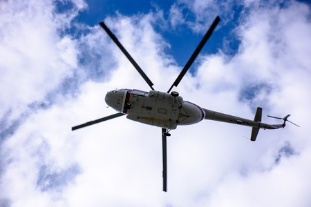 A large helicopter is flying in the blue sky.