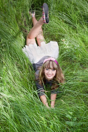 Beautiful girl lying on green grass and smiling photo