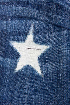 Star-shaped patch on jeans closeup, front view Stock Photo