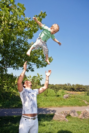 Father throws the boy in the park