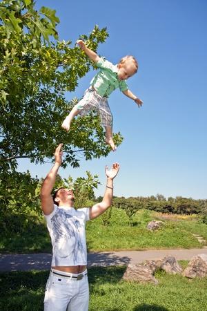Vater wirft den Jungen im Park