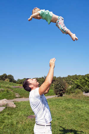 Father throwing his son into the air Stock Photo - 12534139