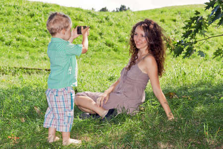 Son photographing his beautiful mother in the park a mobile phone Stock Photo - 12534163