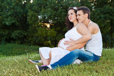 man and his pregnant wife were sitting on the lawn Stock Photo - 12844890