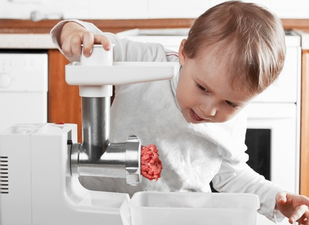 Meat Grinders , little boy cutting meat Stock Photo - 12845221