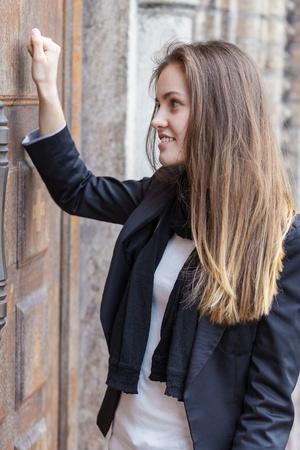 puertas antiguas: Chica llama a la puerta cerrada de la iglesia Foto de archivo