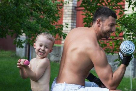 Father and son train with dumbbells outdoors Stock Photo - 13766106