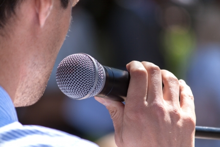 public speaker: Speaker holds the microphone close up