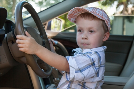A boy wearing a cap while driving Stock Photo