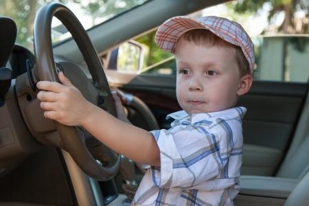 A boy wearing a cap while driving Foto de archivo