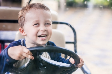 Smiling boy behind the wheel of the electric vehicle photo