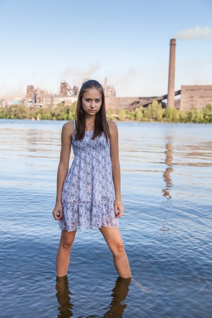 Beautiful girl standing in the water against background steel plant photo