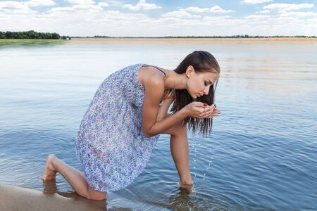 Young woman drinking clean water from Lake photo