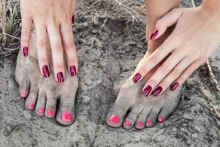 Maniküre und Pediküre auf dem Hintergrund der schmutzigen Sand