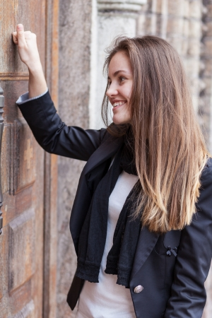 Smiling girl knocks on the closed door of the church photo