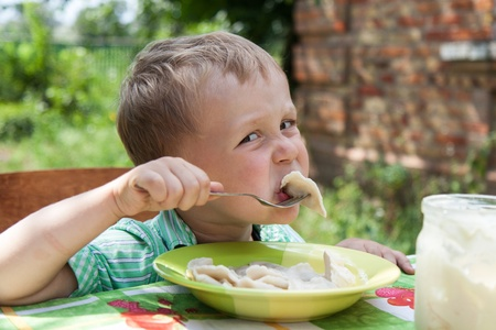Boy eats breakfast outside in countryside Stock Photo - 15171135