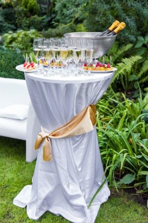 Tabelle mit Champagner und Häppchen auf einer Hochzeit im Freien