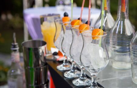 Cocktail glasses with ice cubes, orange and olives photo