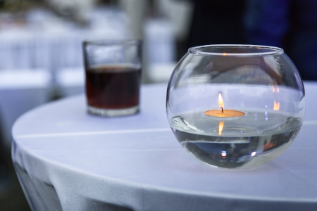 Candle floating in the water and glass of cola in the background Stock Photo