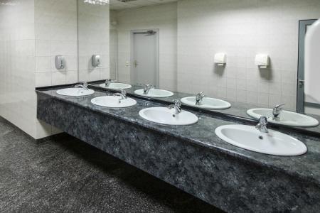 Rij van wastafels met spiegels in openbaar toilet Stockfoto