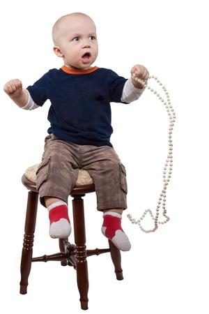 Junge spielt Perlenkette, isoliert auf weißem Hintergrund