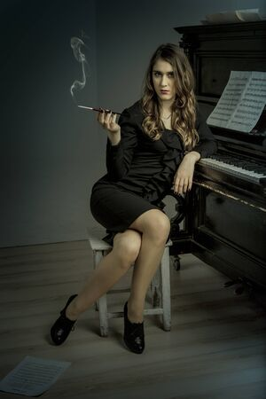 Young woman smoking cigarette near old piano photo