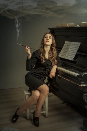 Junge Frau Rauchen Zigarette in der Nähe altes Klavier