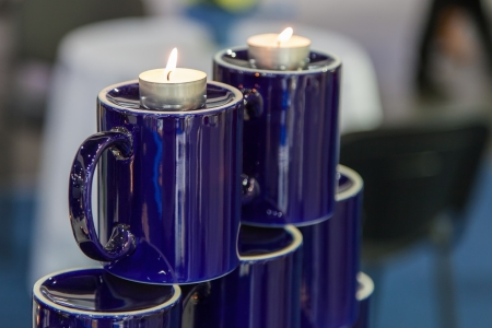 Two burning candles standing on upturned cups photo