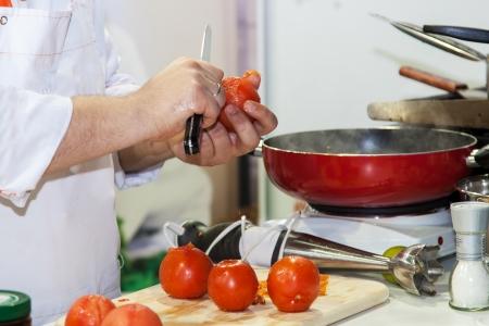 Küchenchef bereitet Tomaten für vegetarische Mahlzeiten Standard-Bild