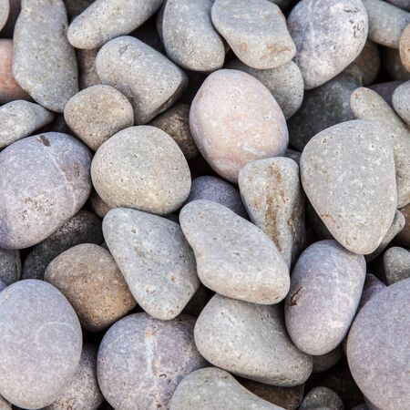 Pebbles as a background stony texture, in a square photo