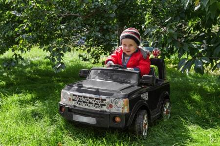 Smiling boy at the wheel toy electromobile Stock Photo
