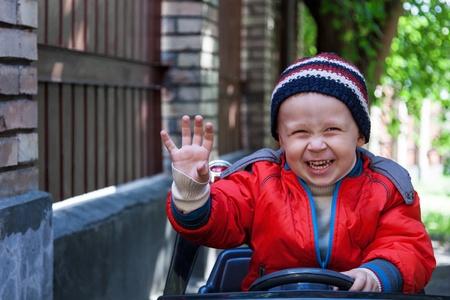 Smiling boy at the wheel toy electromobile photo
