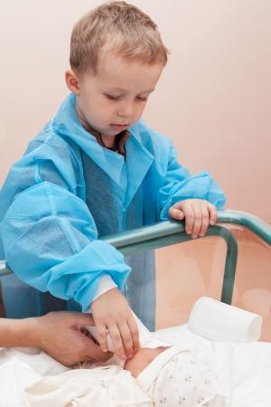 Boy hilft füttern seine neugeborene Schwester aus einer Flasche in der Geburtsklinik