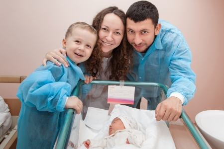 Happy family; father, mother, and son bending over their newborn daughter in the maternity hospital photo