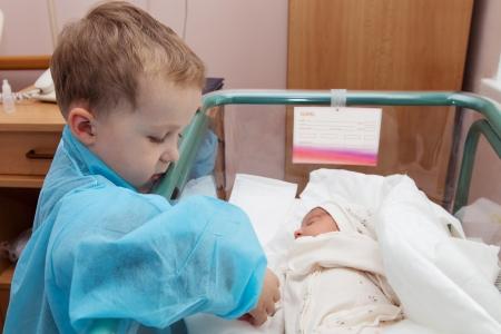 Der Junge schaut auf seine neugeborene Schwester in der Entbindungsklinik